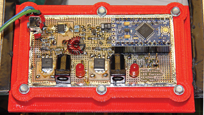 The power switch components occupy the upper left corner of the PCB, with the Hall effect current sensor near the middle and the Arduino Pro Mini board to the upper right. The 3-D printed red frame stiffens the circuit board during construction.