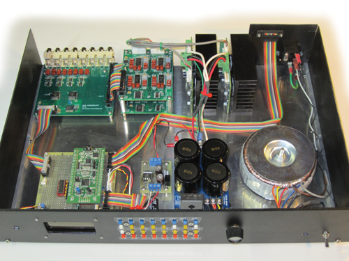 Photo 1: Clockwise from the upper left, the whole-house system includes the crosspoint board, two quad preamplifiers, two two-zone stereo amplifiers, an AC transformer, power supplies, and the CPU board with the STMicroelectronics STM32VLDISCOVERY board.