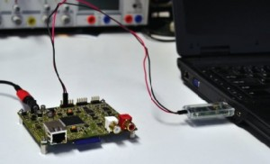 Thaidmer Riemersma's trace dongle is connected to a laptop and device. The dongle decodes the signal and forwards it as serial data from a virtual RS-232 port to the workstation.
