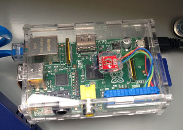 This is the final installation of the Raspberry Pi. The clear acrylic case can be seen along with the TMP102 glued below the air hole drilled into the case. A ribbon cable was modified to connect the various pins of the TMP102 to the Raspberry Pi.