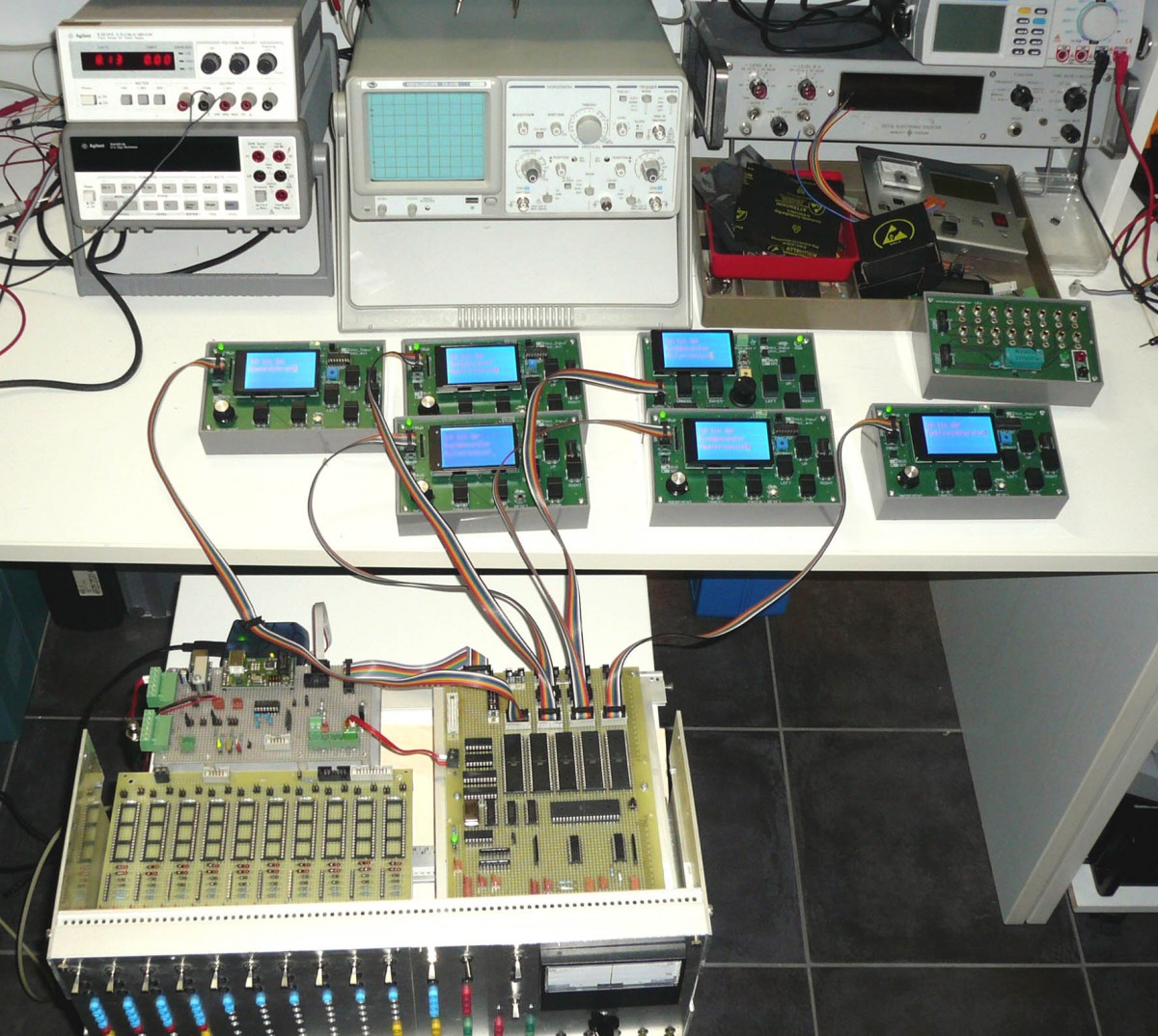 Real work is shown here at the digital analog computer—bring-up and debugging of the master controller board. Each of the six microcontrollers is connected to a general-purpose human-interface module.