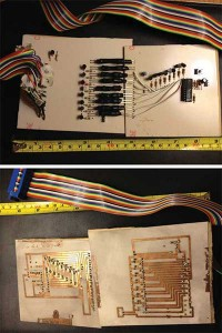 Andrew worked on this project when computers still had parallel ports. a—This photo shows manually etched PCB traces for a digital EKG (the attempted EEG) with 8-bit LED optoisolation. The rainbow cable connects to a computer's parallel port. The interface code was written in C++ and ran on DOS. b—The EKG circuitry and digitizer are shown on the left. The 8-bit parallel computer interface is on the right. Connecting the two boards is an array of coupled LEDs and phototransistors, encased in heat shrink tubing to shield against outside light.