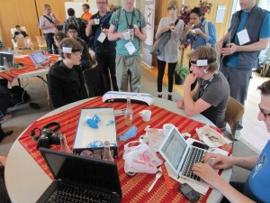 This photo was taken in the Open Source Bridge hacker lounge, where people socialize and collaborate on projects. Here someone brought a brainwave-control game. The players are wearing electroencephalography (EEG) readers, which are strapped to their heads. The goal of the game is to use biofeedback to move the floating ball to your opponent's side of the board.