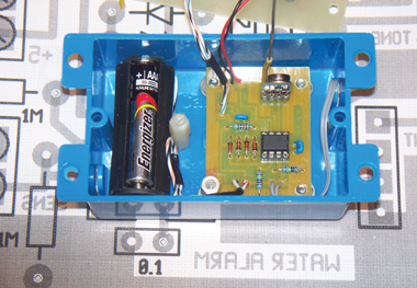 "Photo 3: This is the water alarm's interior. The transmitter module with its antenna can be seen in the upper right. The battery holder was harvested from a $1 LED flashlight. The box is 2.25"" × 3.5"", excluding the tabs."