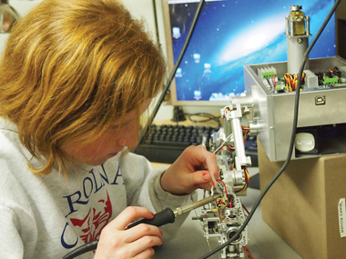 Photo 4: Beatty Robotics is a family of makers that produces some incredible models. Young Camille Beatty handles the soldering, but is also well-versed in machining and other areas of expertise.