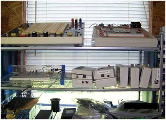 Bellerose's Protostation, purchased on eBay, is on top shelf (left). He designed the setup on the right, which includes a voltmeter, a power supply, and transistor-transistor logic (TTL) oscillators. A second protoboard unit is on the middle shelf (left). On the right are various Intersil ICM7216D frequency-counter units and DDS-based signal generator units from eBay. The bottom shelf is used for protoboard storage.