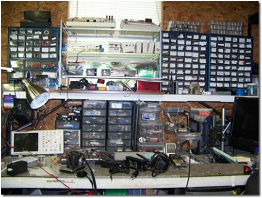 The main workbench has a 4′-by-6′ center rack and parts storage units on the left and right. The main bench includes an OWON 25-MHz oscilloscope, storage drawers for lithium-ion (Li-on) batteries (center), voltage converter modules, various project modules on right, a Dremel drill press, and a PC monitor.